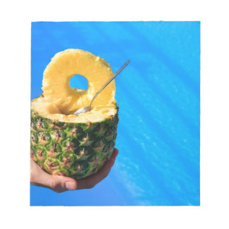 Hand holding fresh pineapple above swimming pool notepad