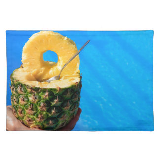 Hand holding fresh pineapple above swimming pool placemat
