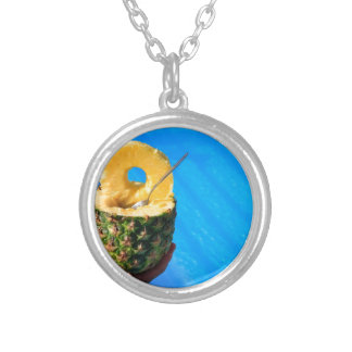 Hand holding fresh pineapple above swimming pool silver plated necklace