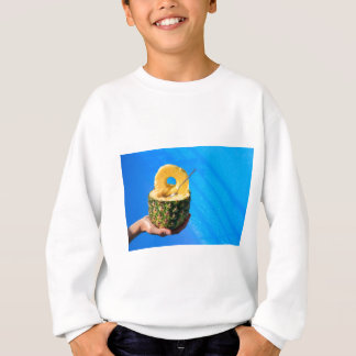 Hand holding fresh pineapple above swimming pool sweatshirt