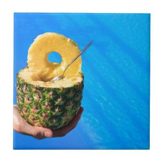 Hand holding fresh pineapple above swimming pool tile