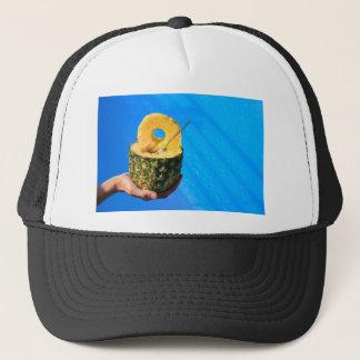 Hand holding fresh pineapple above swimming pool trucker hat