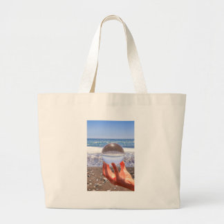 Hand holding glass sphere at beach and sea large tote bag