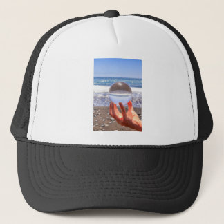 Hand holding glass sphere at beach and sea trucker hat
