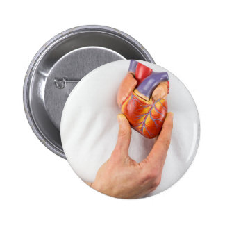 Hand holding model heart on chest 2 inch round button