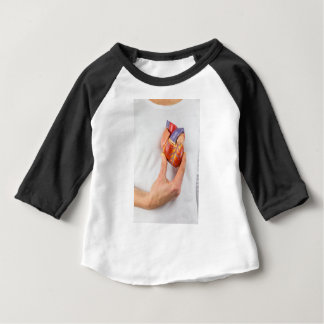 Hand holding model heart on chest baby T-Shirt