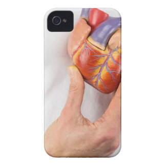 Hand holding model heart on chest iPhone 4 case