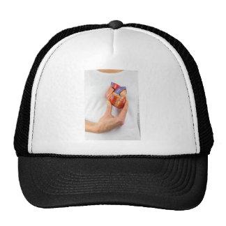 Hand holding model heart on chest trucker hat