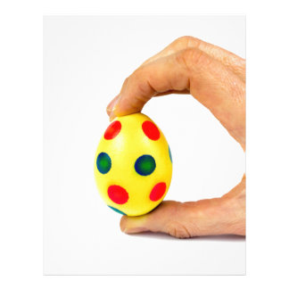 Hand holding painted yellow easter egg with dots customized letterhead