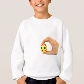Hand holding painted yellow easter egg with dots sweatshirt