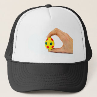 Hand holding painted yellow easter egg with dots trucker hat