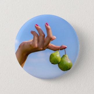 Hand holding two hanging green pears in blue sky 2 inch round button