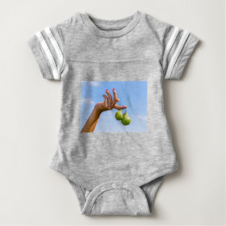 Hand holding two hanging green pears in blue sky baby bodysuit