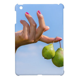 Hand holding two hanging green pears in blue sky case for the iPad mini