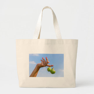 Hand holding two hanging green pears in blue sky large tote bag