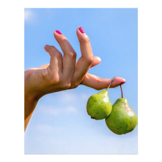 Hand holding two hanging green pears in blue sky letterhead