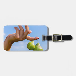 Hand holding two hanging green pears in blue sky luggage tag