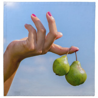Hand holding two hanging green pears in blue sky napkin