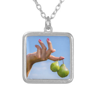 Hand holding two hanging green pears in blue sky silver plated necklace