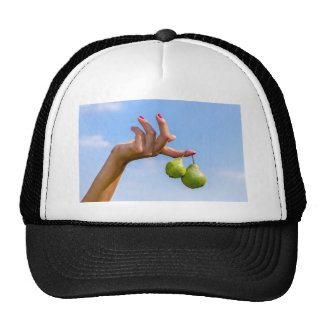 Hand holding two hanging green pears in blue sky trucker hat