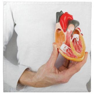Hand holds human heart model at body napkin