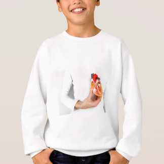 Hand holds human heart model at body sweatshirt