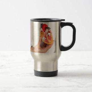 Hand holds human heart model at body travel mug