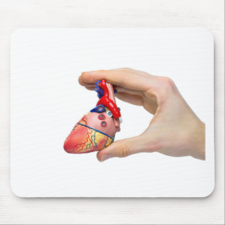 Hand holds model human heart between fingers mouse pad