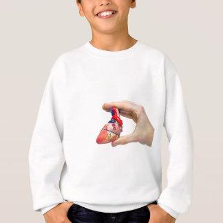 Hand holds model human heart between fingers sweatshirt