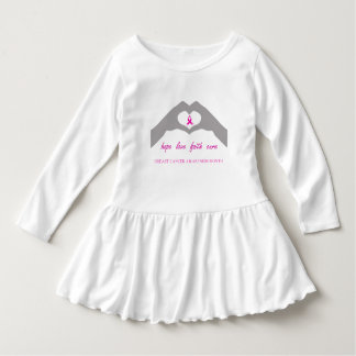 Hand making heart sign with breast cancer ribbon dress