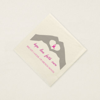 Hand making heart sign with breast cancer ribbon napkin