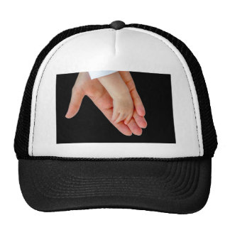 Hand of mother with arm of baby on black trucker hat