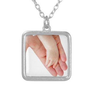 Hand of mother with arm of baby silver plated necklace