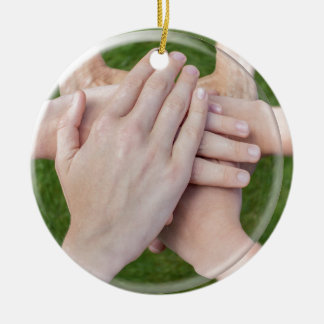 Hands arms uniting in glass sphere round ceramic ornament