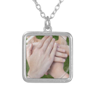 Hands arms uniting in glass sphere silver plated necklace