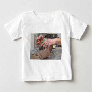 Hands cut out a sculpture from a chocolate baby T-Shirt