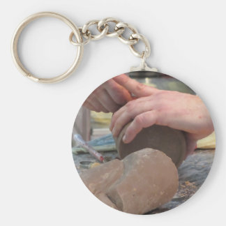 Hands cut out a sculpture from a chocolate basic round button keychain