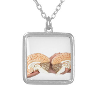 Hands holding model human brain on white silver plated necklace