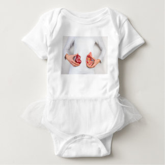 Hands holding model of human kidney organ at body. baby bodysuit