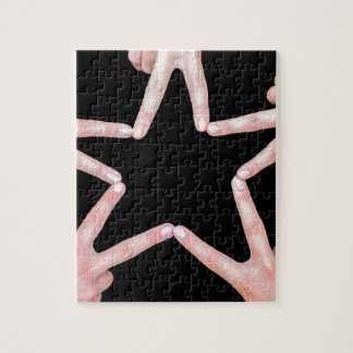 Hands of girls making star shape on black jigsaw puzzle