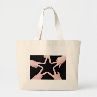 Hands of girls making star shape on black large tote bag
