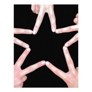 Hands of girls making star shape on black letterhead