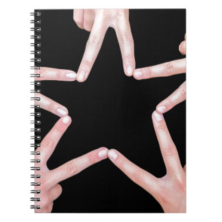 Hands of girls making star shape on black notebook