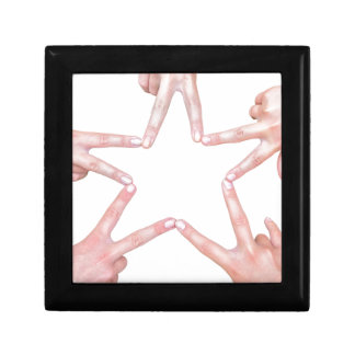 Hands of girls making star shape on white gift box