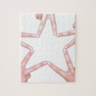 Hands of girls making star shape on white jigsaw puzzle