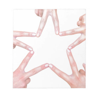 Hands of girls making star shape on white notepad
