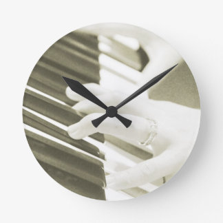 hands playing the piano photograph sepia round clock