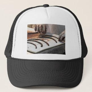 Hands preparing chocolate decoration on a worktop trucker hat