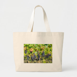 Hanging blue grape bunches in vineyard large tote bag