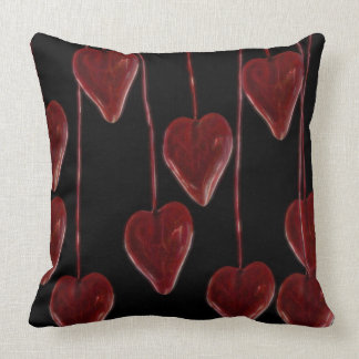 Hanging heart's on a black throw pillow
